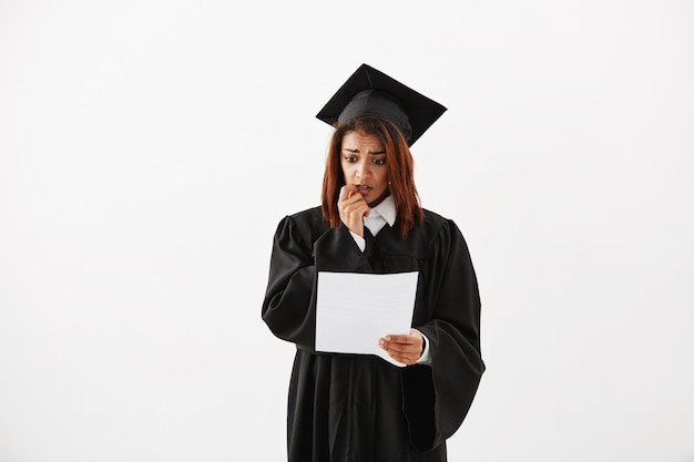 Retrato de triste confuso inseguro descontente graduado universidade feminina africana se preparando para seu discurso de aceitação ou segurando o teste.