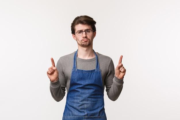 Retrato de triste e indiferente jovem entediado trabalhando café ou restaurante sobre balcão de bar, usar avental, careta incomodado e chateado como apontando para algo decepcionante