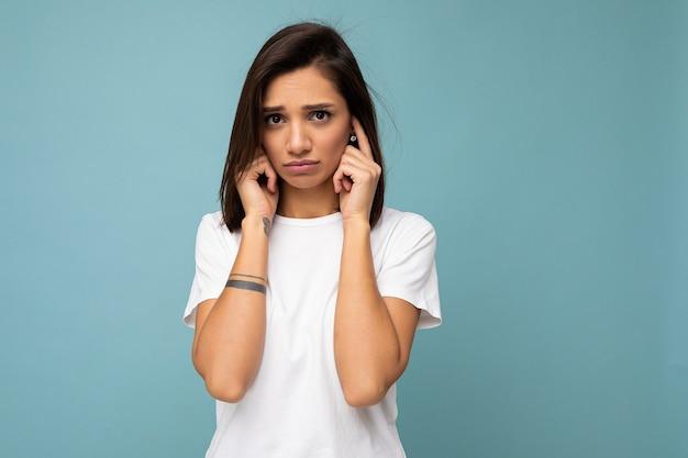 Retrato de triste triste jovem muito legal morena com emoções sinceras, vestindo camiseta branca casual para maquete isolado em um fundo azul com espaço de cópia e cobrindo as orelhas com os dedos.