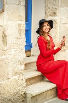 Retrato de turista jovem mulher caucasiana em um vestido longo vermelho e chapéu preto com mala sentado na escada ao ar livre.