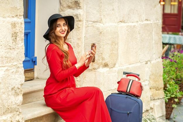 Retrato de turista jovem mulher caucasiana em um vestido longo vermelho e chapéu preto com mala sentado.