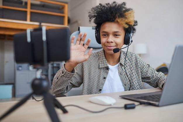 Retrato de um adolescente afro-americano usando fone de ouvido e acenando para a câmera enquanto transmite videogames em casa, conceito de jovem jogador ou blogueiro, copie o espaço