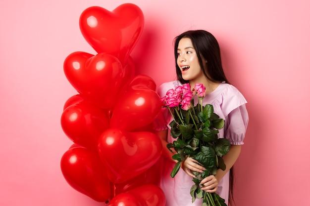 Retrato de um adolescente asiático apaixonado, segurando flores e olhando para os balões de coração do dia dos namorados, estando num encontro romântico, fundo rosa.