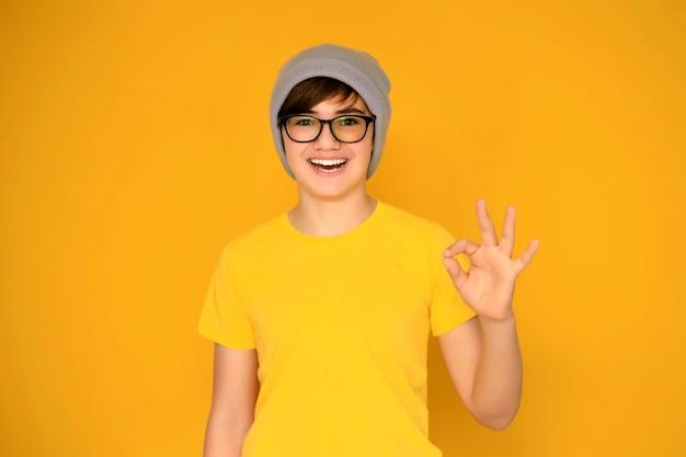 Retrato de um adolescente bonito de 12 a 13 anos em um fundo amarelo.