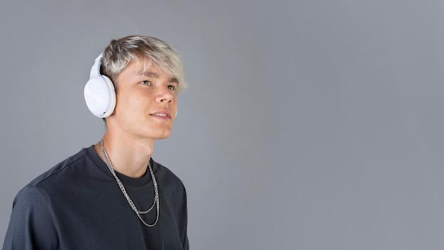 Retrato de um adolescente descolado ouvindo música em fones de ouvido