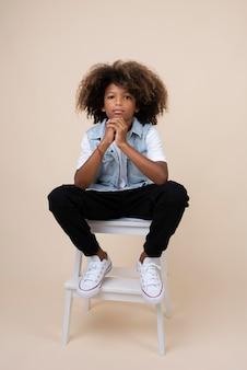 Retrato de um adolescente descolado posando em uma cadeira