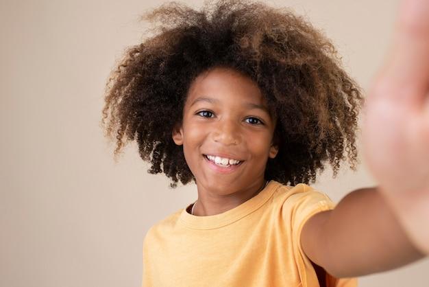 Retrato de um adolescente descolado tirando uma selfie