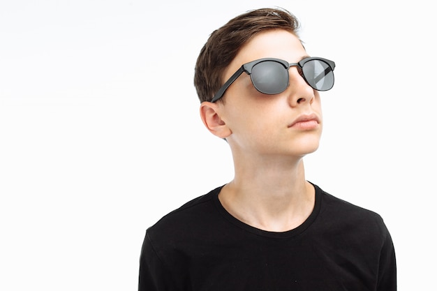Retrato de um adolescente elegante com óculos de sol em uma camisa preta