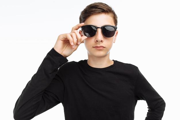 Retrato de um adolescente elegante com óculos em uma camiseta preta
