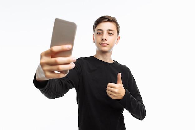 Retrato de um adolescente emocional que tira uma selfie em um smartphone
