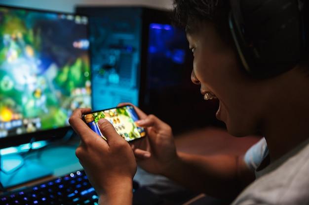 Retrato de um adolescente feliz jogando videogame no smartphone e no computador em um quarto escuro, usando fones de ouvido e um teclado colorido com luz de fundo Foto Premium