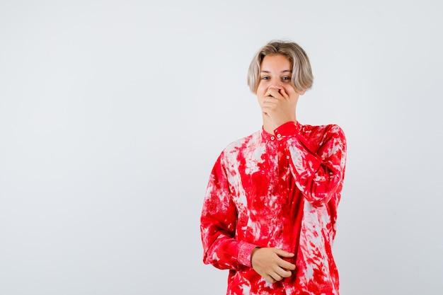 Retrato de um adolescente loiro masculino cobrindo a boca com a mão em uma camisa grande e olhando frontalmente bem-aventurada