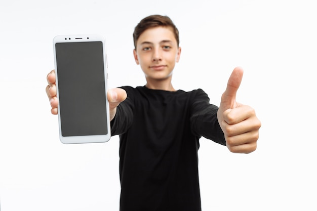 Retrato de um adolescente segurando um telefone com uma tela branca