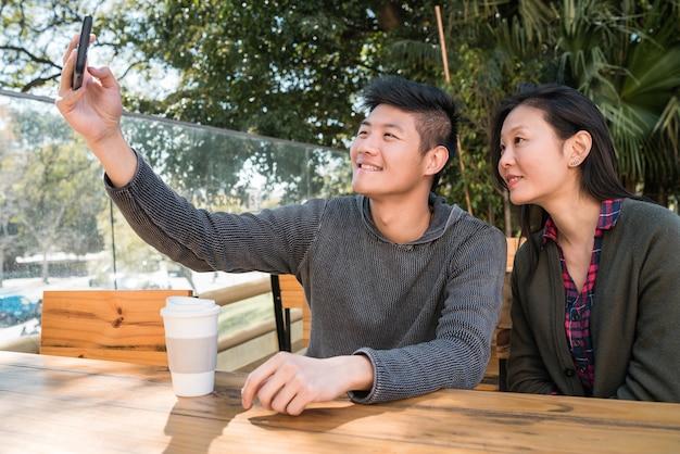 Retrato de um adorável casal asiático se divertindo e tirando uma selfie com o celular em uma cafeteria