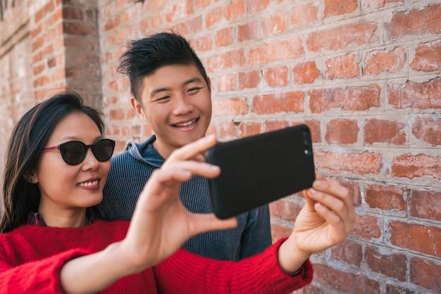 Retrato de um adorável casal asiático tirando uma selfie com o celular ao ar livre na rua