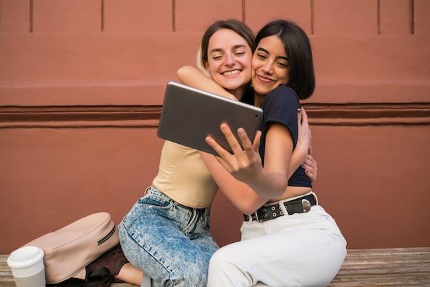 Retrato de um adorável casal de lésbicas passando um tempo juntos e tirando uma selfie com tablet digital ao ar livre