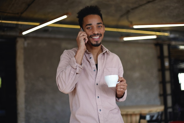 Retrato de um adorável jovem barbudo com pele escura, olhando alegremente com um sorriso largo e encantador, bebendo chá e fazendo ligações com seu telefone celular, vestido com uma camisa bege