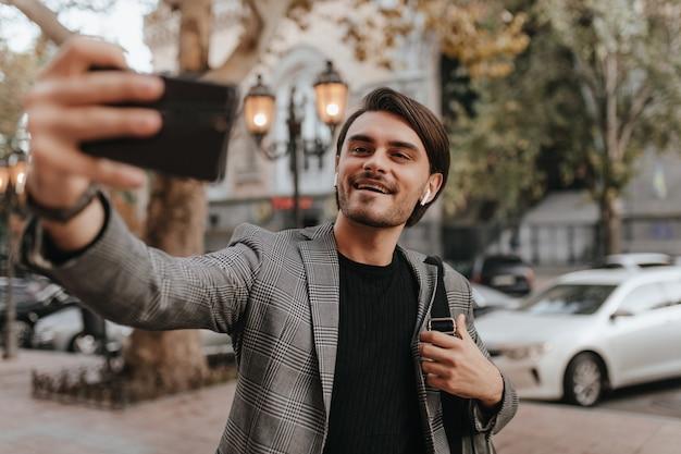 Retrato de um adorável jovem cavalheiro em camiseta preta e blazer vintage xadrez, fazendo selfie contra a parede do marco da cidade e sorrindo