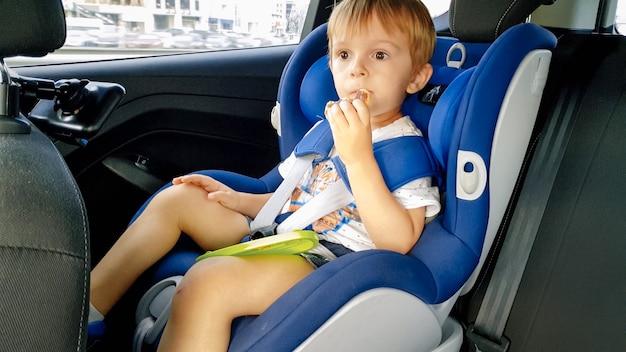 Retrato de um adorável menino sentado na cadeirinha infantil e comendo biscoitos