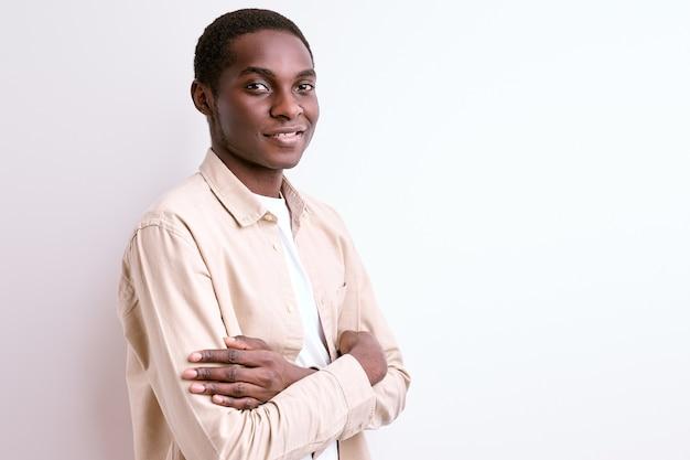 Retrato de um africano confiante em pé com os braços cruzados e sorrindo