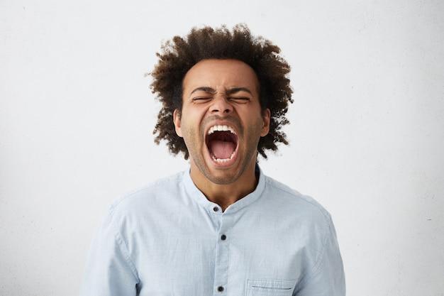 Retrato de um africano de pele escura com cabelo encaracolado gritando com a boca bem aberta