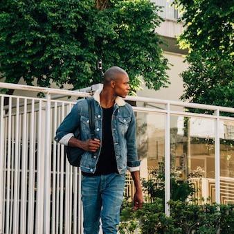Retrato, de, um, africano, homem jovem, com, seu, mochila, ligado, ombro, olhando