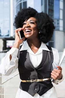 Retrato, de, um, africano, jovem, executiva, falando telefone móvel