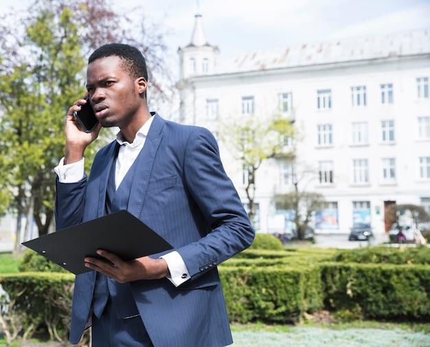 Retrato, de, um, africano, jovem, executiva, segurando clipboard, falando telefone móvel