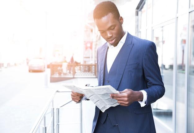 Retrato, de, um, africano, jovem, homem negócios fica, exterior, a, escritório, lendo jornal