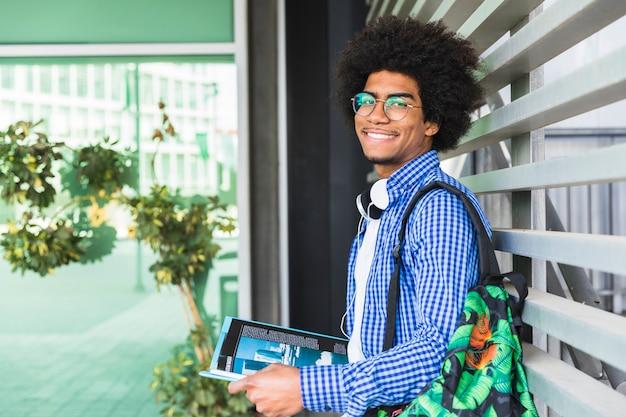 Retrato, de, um, africano, sorrindo, estudante masculino, inclinar-se, parede