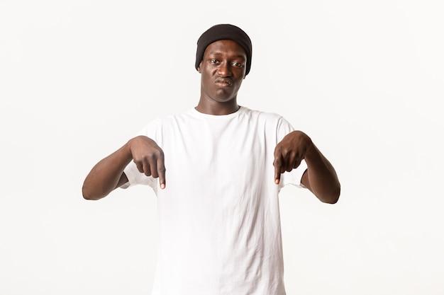 Retrato de um afro-americano cético e decepcionado reclamando, apontando o dedo para baixo e fazendo uma careta incomodado