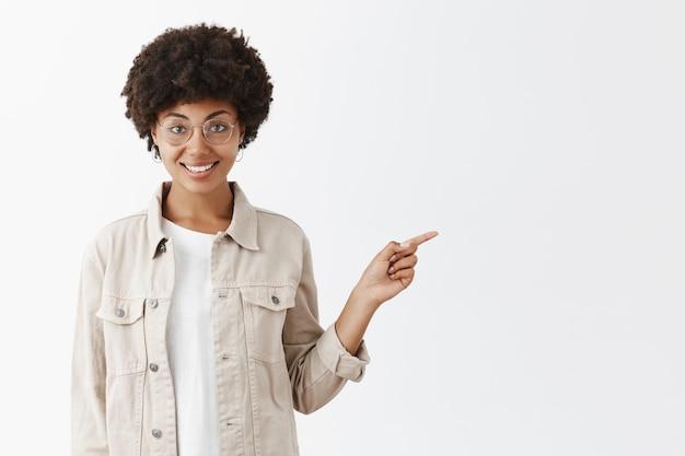 Retrato de um afro-americano encantador de óculos e camisa com penteado afro, apontando para a direita com o dedo indicador e sorrindo