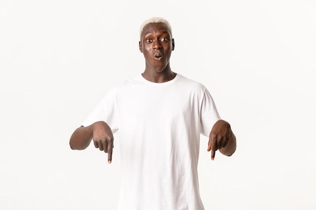 Retrato de um afro-americano fascinado e espantado com cabelos loiros, apontando os dedos para baixo e arfando e maravilhado