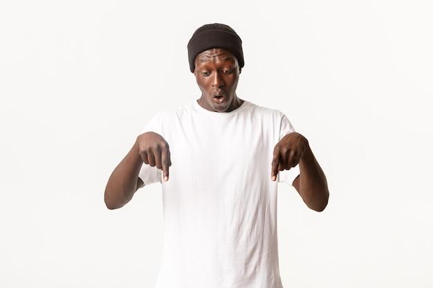 Retrato de um afro-americano maravilhado e surpreso com um gorro, um homem bonito apontando o dedo para baixo e parecendo surpreso