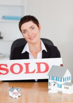 Retrato de um agente imobiliário com um painel vendido e casas de miniaturas