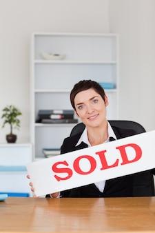 Retrato de um agente imobiliário com um painel vendido