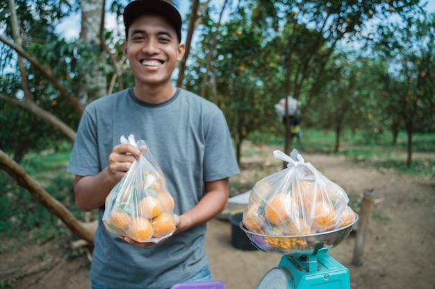 Retrato de um agricultor feliz vendendo frutas de laranja com saco plástico