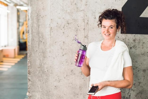 Retrato, de, um, ajuste, mulher, com, smartphone, e, garrafa água