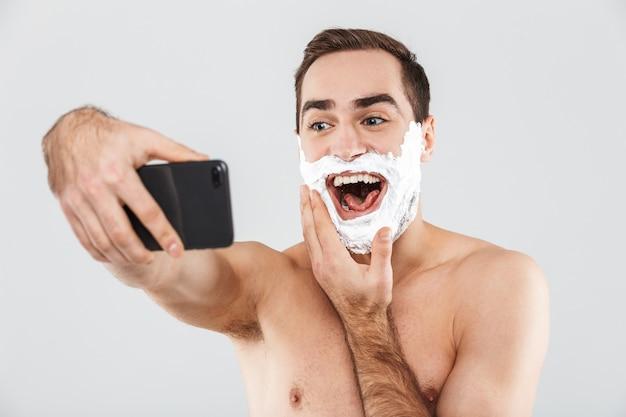 Retrato de um alegre homem barbudo sem camisa, isolado sobre o branco, o rosto coberto com espuma de barbear, tirando uma selfie