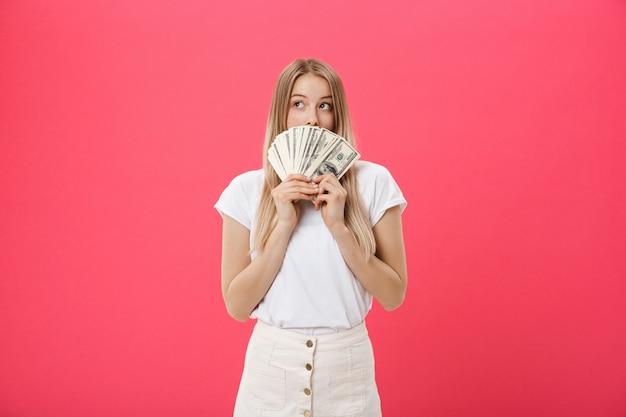 Retrato, de, um, alegre, mulher jovem, segurando, dinheiro, notas, e, celebrando, isolado, sobre, fundo cor-de-rosa