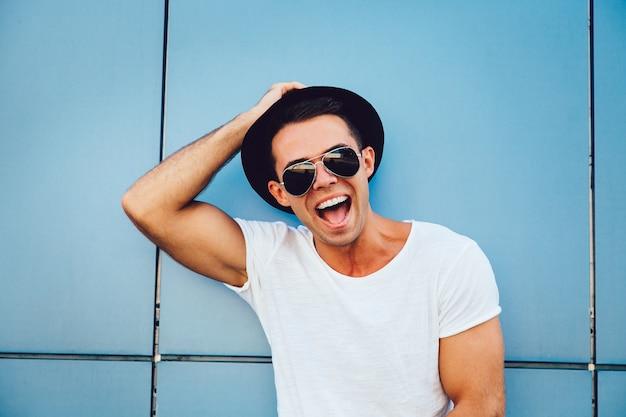 Retrato, de, um, alegre, músculo, sujeito, em, óculos de sol, e, chapéu, olhando câmera, e, sorrindo, extensamente