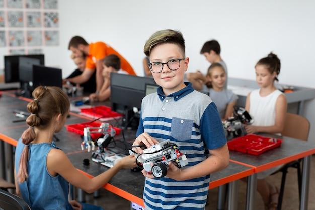 Retrato de um aluno do sexo masculino construindo um veículo robô na aula de programação de computador após a aula