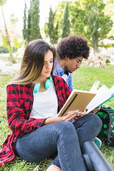 Retrato, de, um, aluno feminino, sentando, com, dela, amigo, estudar, junto, em, parque