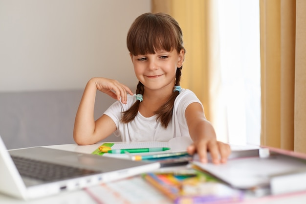Retrato de um aluno sorridente feliz, vestindo camiseta branca, sentado à mesa contra a janela com cortinas na frente do laptop, tendo uma expressão positiva, fazendo a lição de casa.