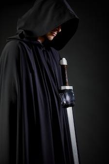 Retrato de um andarilho guerreiro corajoso em uma capa preta e espada na mão.