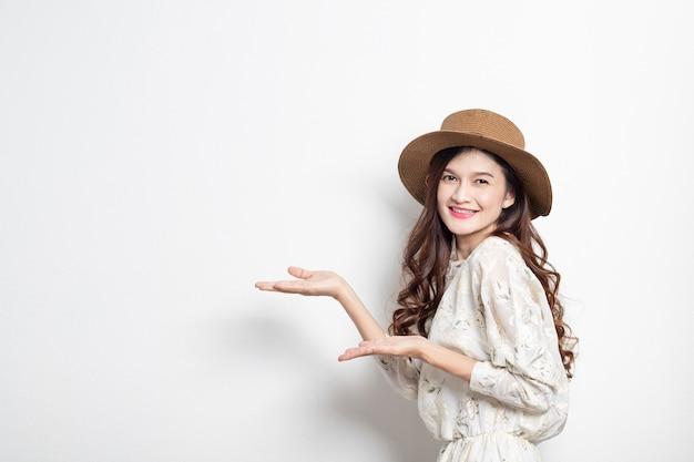 Retrato de um apresentador asiático de sorriso da mulher no fundo branco, mulher asiática que aponta ao espaço da cópia, menina tailandesa bonita.