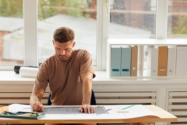Retrato de um arquiteto barbudo bonito olhando as plantas enquanto está sentado na mesa de desenho à luz do sol,
