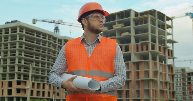 Retrato de um arquiteto ou construtor em pé na frente do prédio em construção.