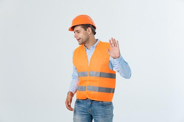 Retrato de um arquiteto ou designer masculino confuso, sente-se estressado, nervoso, mantém a mão na cabeça, encara a planta. homem exausto cria projeto de construção sozinho, tem alguns problemas