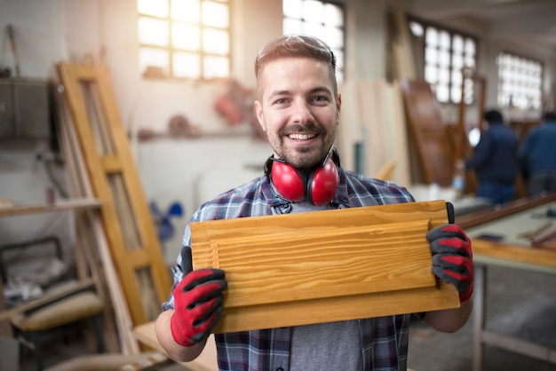 Retrato de um artesão sorridente segurando um móvel em sua oficina de carpintaria